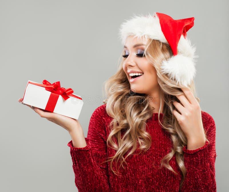 Γυναίκα Χριστουγέννων στο άσπρο κιβώτιο δώρων Χριστουγέννων εκμετάλλευσης καπέλων Santa στοκ εικόνες