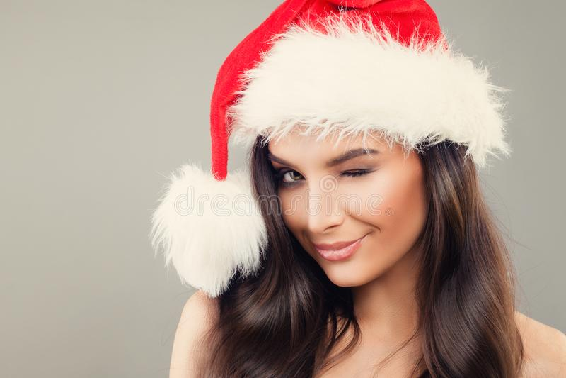 Γυναίκα Χριστουγέννων στο κλείσιμο του ματιού καπέλων Santa στοκ εικόνα