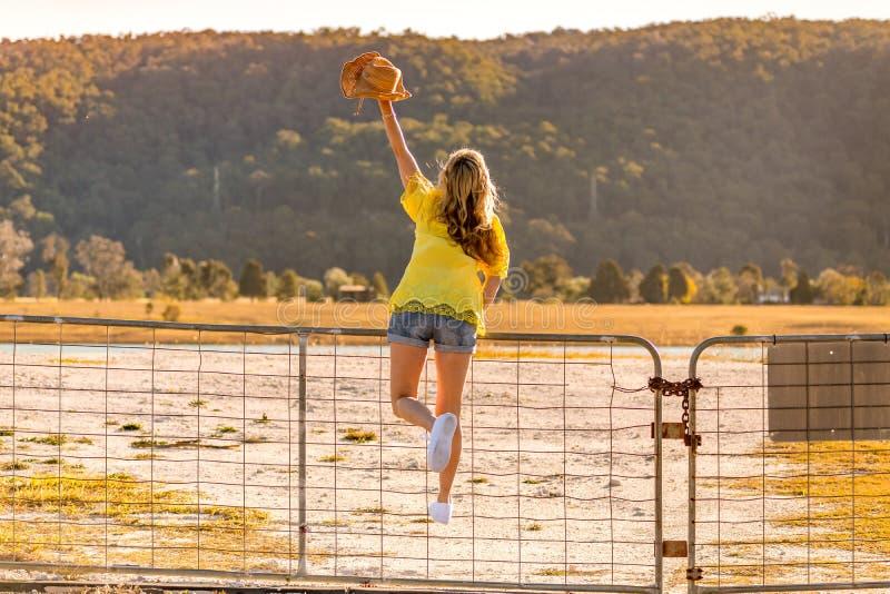 Γυναίκα Aussie που στέκεται σε μια πύλη αγροκτημάτων στοκ φωτογραφία με δικαίωμα ελεύθερης χρήσης