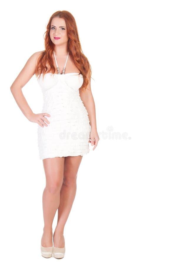 Γυναίκα Beautuful με την κόκκινη μακρυμάλλη τοποθέτηση στο άσπρο φόρεμα στοκ εικόνα με δικαίωμα ελεύθερης χρήσης