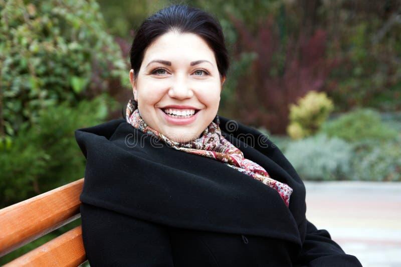 Γυναίκα brunette ευτυχίας σε έναν πάγκο στοκ εικόνα