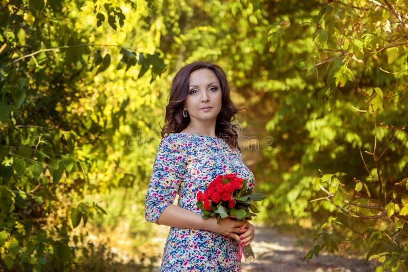 Γυναίκα Brunette με τα κόκκινα τριαντάφυλλα στοκ εικόνα με δικαίωμα ελεύθερης χρήσης