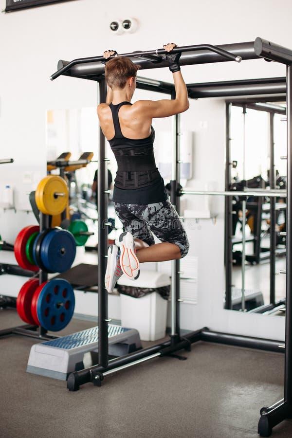 Γυναίκα Brunette με την κοντή τρίχα, που κάνει workout τη σκλήρυνση στο φραγμό στοκ φωτογραφίες με δικαίωμα ελεύθερης χρήσης