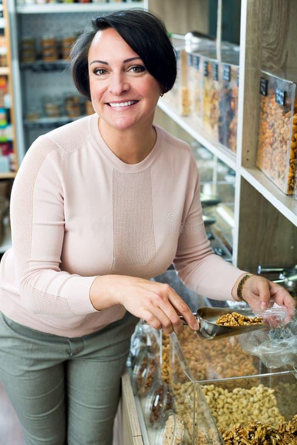 Γυναίκα Brunette που επιλέγει τα καρύδια στοκ εικόνες
