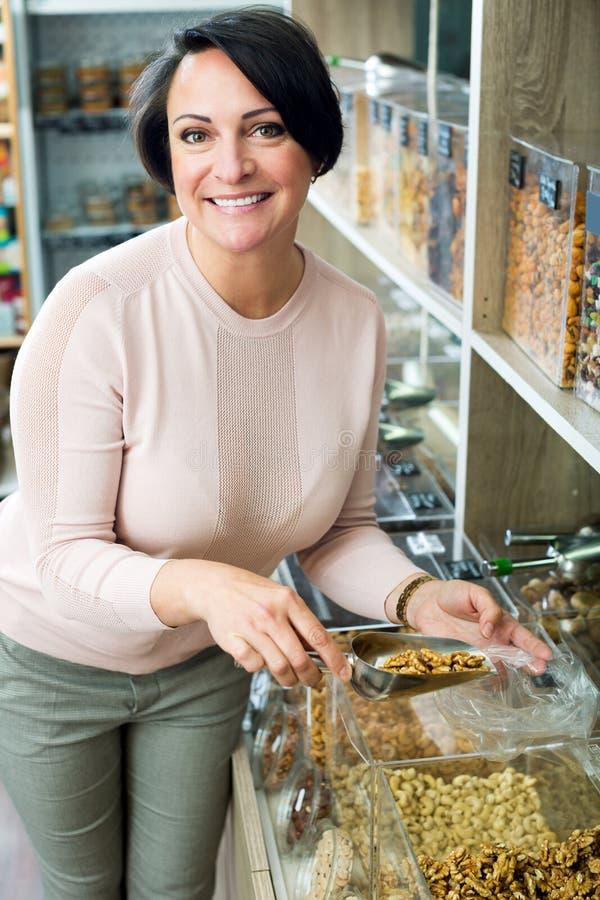 Γυναίκα Brunette που επιλέγει τα καρύδια στοκ φωτογραφίες με δικαίωμα ελεύθερης χρήσης