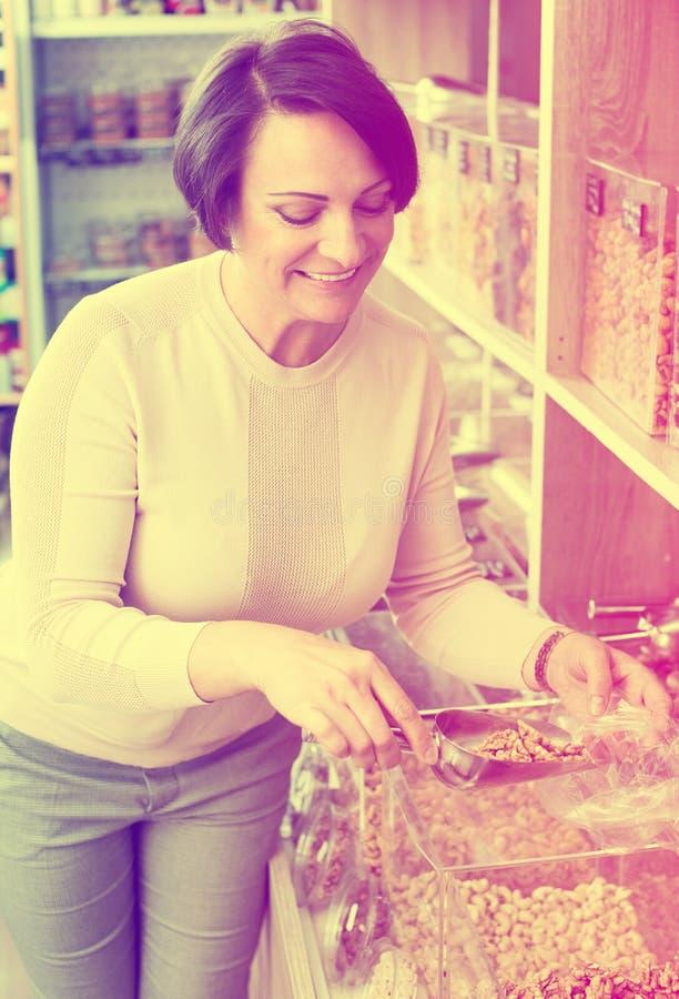 Γυναίκα Brunette που επιλέγει τα καρύδια στοκ εικόνα