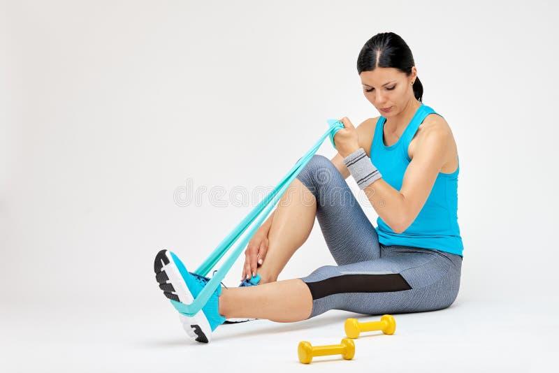 Γυναίκα Brunette που κάνει τις ασκήσεις με τη λαστιχένια ζώνη στοκ εικόνες