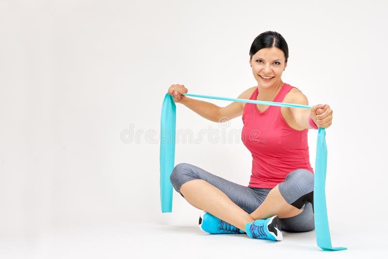 Γυναίκα Brunette που κάνει τις ασκήσεις με τη λαστιχένια ζώνη στοκ φωτογραφίες