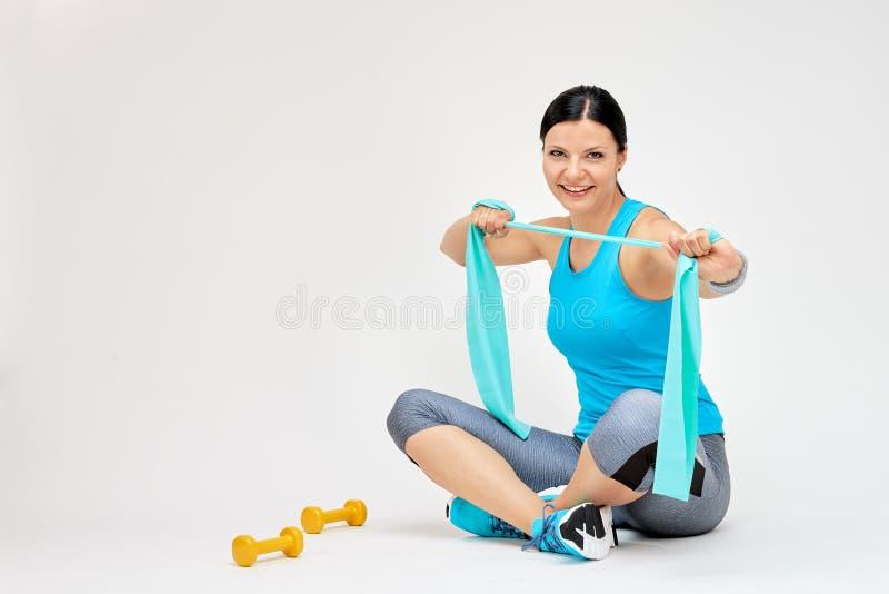 Γυναίκα Brunette που κάνει τις ασκήσεις με τη λαστιχένια ζώνη στοκ εικόνα με δικαίωμα ελεύθερης χρήσης