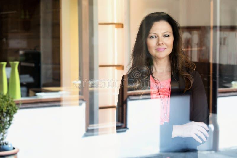 Γυναίκα Brunette που υπερασπίζεται το παράθυρο και το χαμόγελο στοκ εικόνα με δικαίωμα ελεύθερης χρήσης