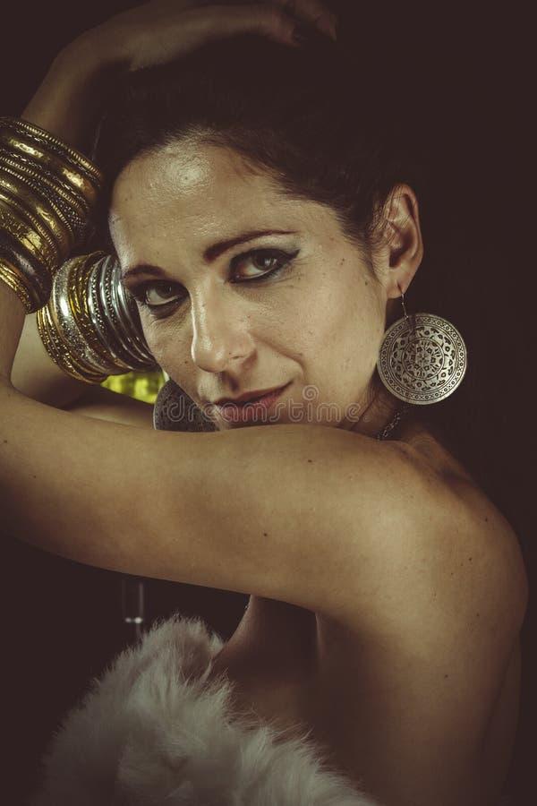 Γυναίκα Brunette που φορά την άσπρη γούνα και το χρυσό κόσμημα στοκ εικόνα με δικαίωμα ελεύθερης χρήσης