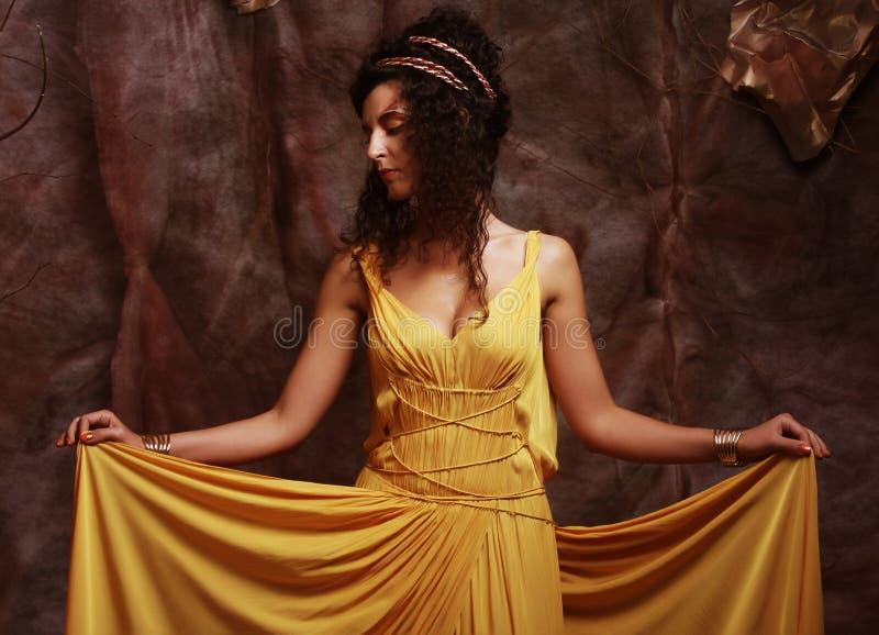 Γυναίκα Brunette που φορά το κίτρινο φόρεμα βραδιού στοκ φωτογραφία