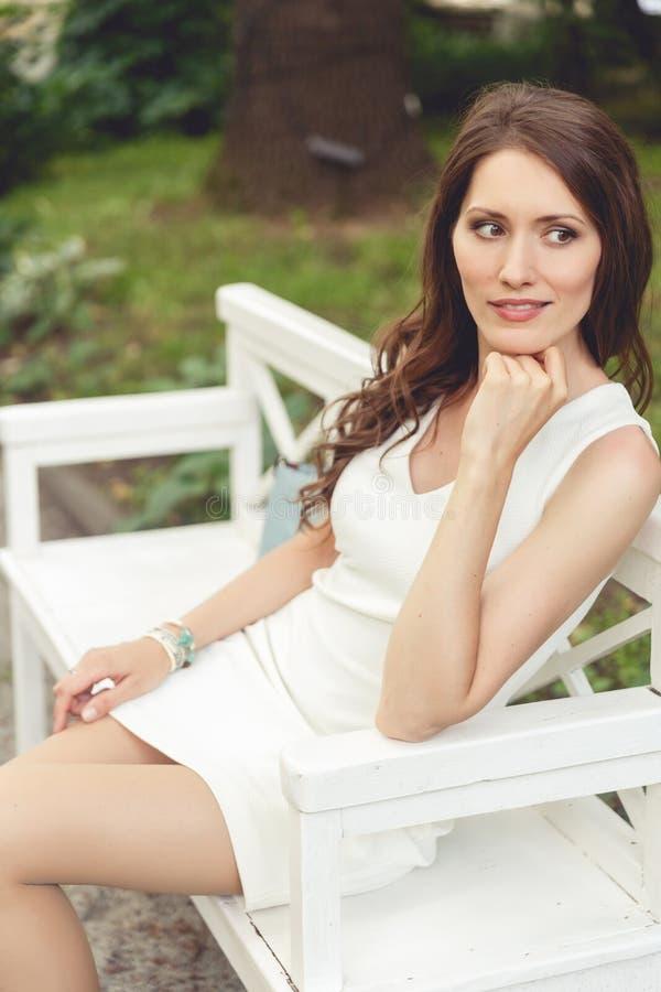 Γυναίκα Brunette στην άσπρη συνεδρίαση φορεμάτων στον πάγκο στο πάρκο στοκ εικόνες με δικαίωμα ελεύθερης χρήσης