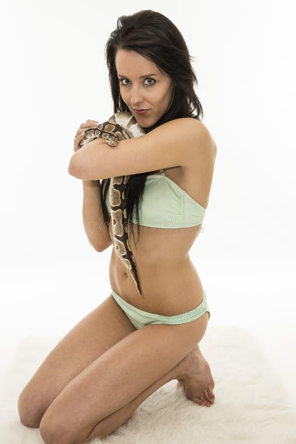 Γυναίκα Brunette στο μπικίνι με το φίδι στον άσπρο τάπητα στοκ φωτογραφία