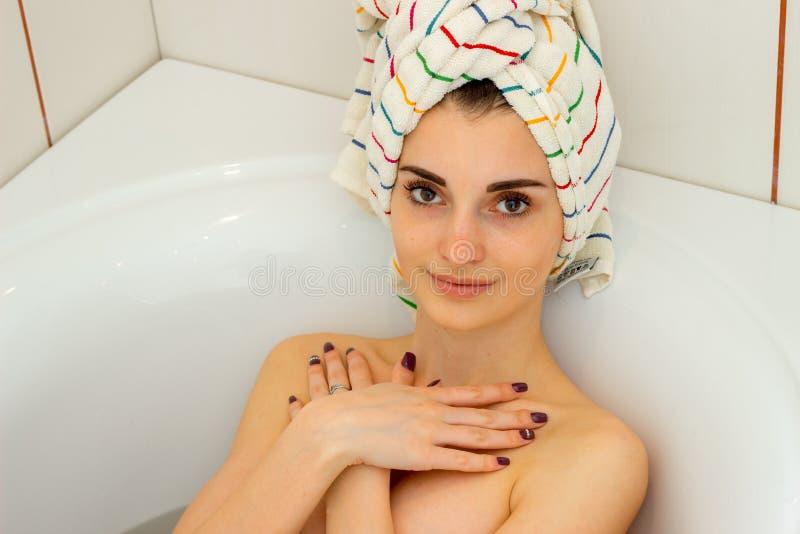 Γυναίκα Brunette στο λουτρό με μια πετσέτα στο κεφάλι στοκ εικόνες με δικαίωμα ελεύθερης χρήσης