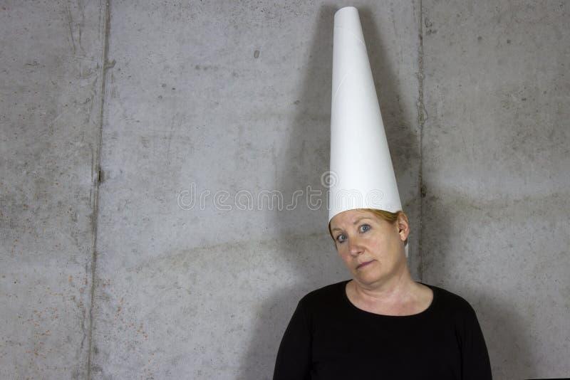 Γυναίκα Dunce ΚΑΠ, κενός τοίχος στοκ εικόνες