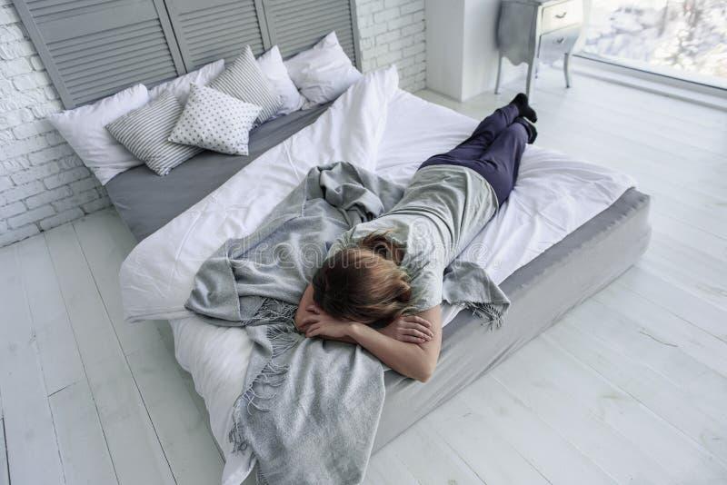 Γυναίκα Forworn που βρίσκεται στο πλαίσιο κρεβατιού στοκ εικόνα με δικαίωμα ελεύθερης χρήσης