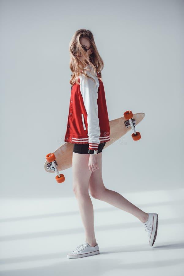 Γυναίκα Hipster με το longboard που περπατά στο στούντιο στο γκρι στοκ φωτογραφία
