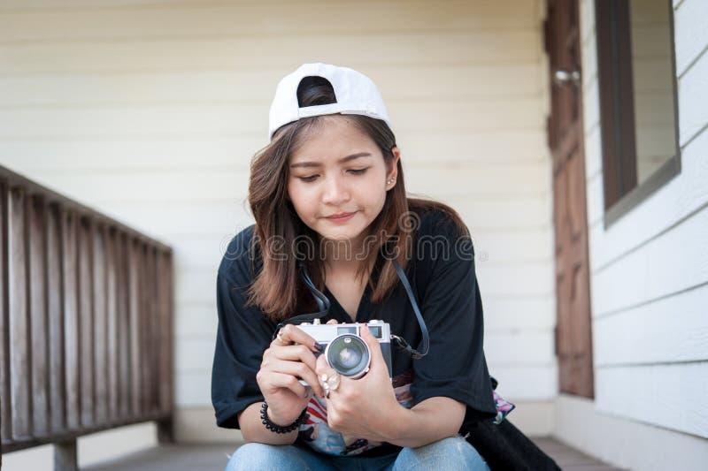 Γυναίκα Hipster που παίρνει τις φωτογραφίες με την αναδρομική κάμερα ταινιών στο ξύλινο πάρκο πόλεων floorof, όμορφο κορίτσι που  στοκ εικόνες