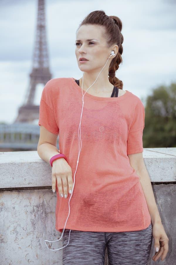 Γυναίκα jogger που εξετάζει την απόσταση και που ακούει τη μουσική στοκ εικόνες