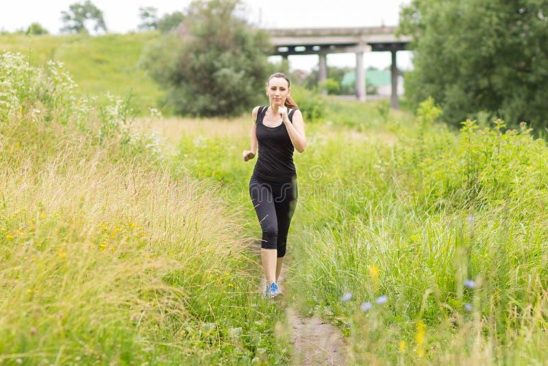 Γυναίκα Jogging στη θερινή μεσημβρία στοκ εικόνες