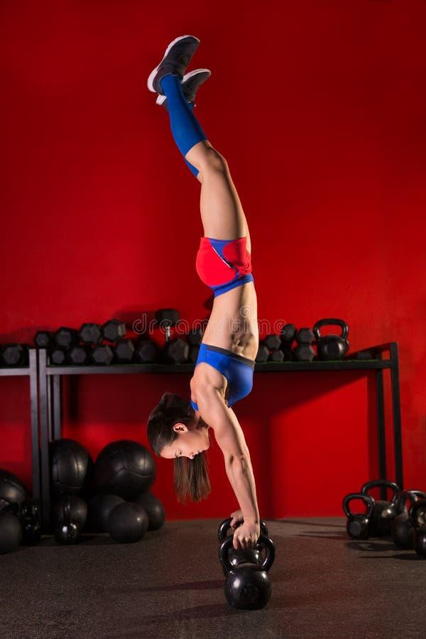 Γυναίκα Kettlebell handstand workout στην κόκκινη γυμναστική στοκ εικόνα