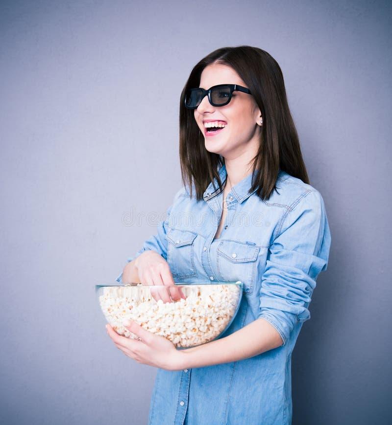 Γυναίκα Lauhging στα γυαλιά κινηματογράφων που κρατά το κύπελλο με popcorn στοκ εικόνες