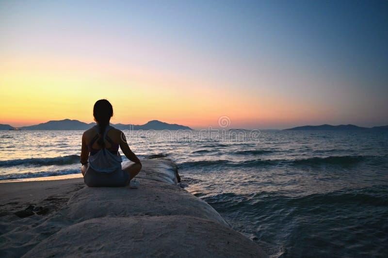 Γυναίκα meditates - χαλαρώνει στο ηλιοβασίλεμα θαλασσίως στην παραλία Έννοια για τη γιόγκα, την υγεία και τη SPA στοκ φωτογραφία