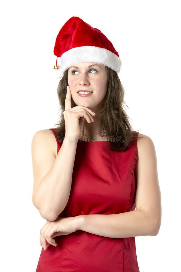 Γυναίκα Santa με το δάχτυλο στο μάγουλο στοκ εικόνα
