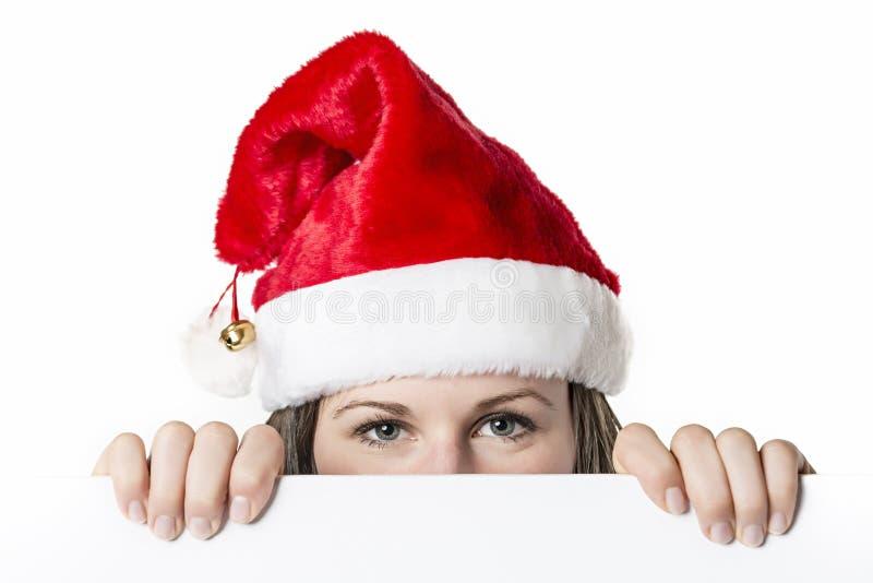 Γυναίκα Santa πίσω από τον πίνακα στοκ εικόνες