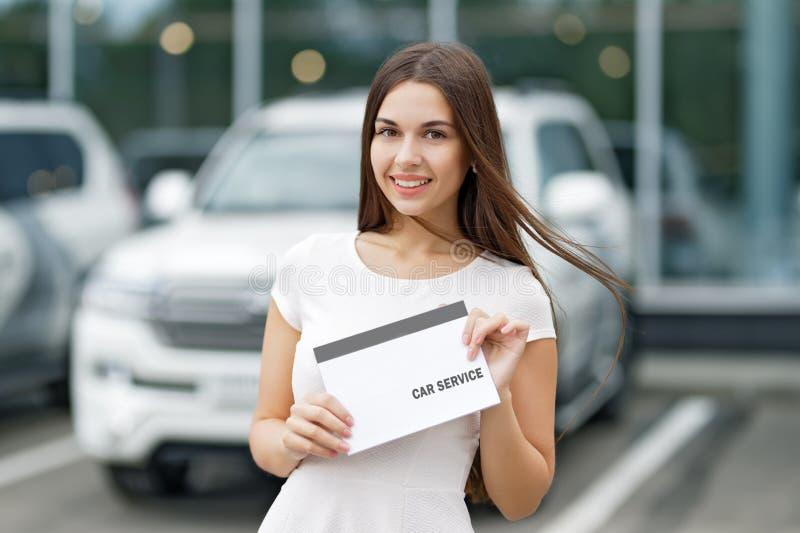 Γυναίκα Smilling με την υπηρεσία αυτοκινήτων συμφωνίας στοκ φωτογραφία