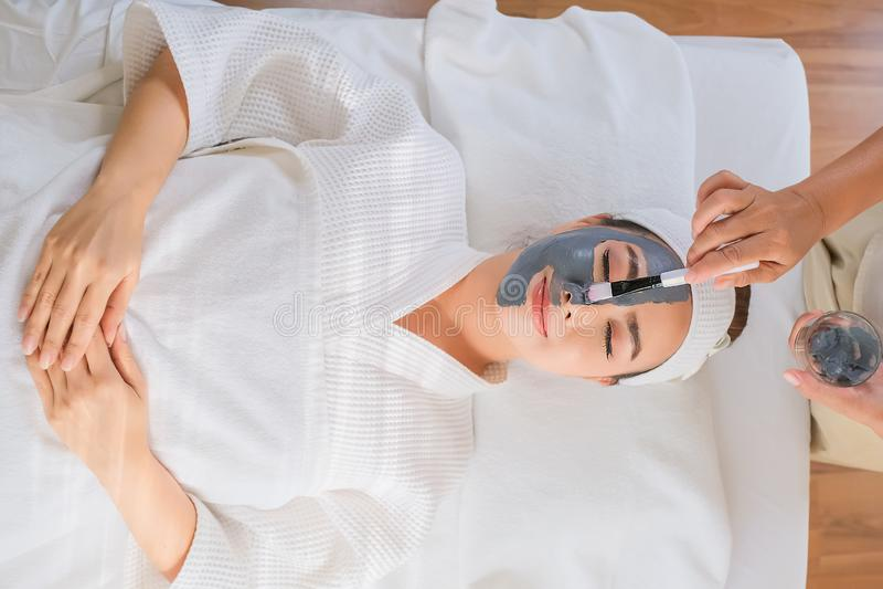 Γυναίκα SPA που εφαρμόζει τις του προσώπου επεξεργασίες ομορφιάς μασκών αργίλου στοκ φωτογραφία
