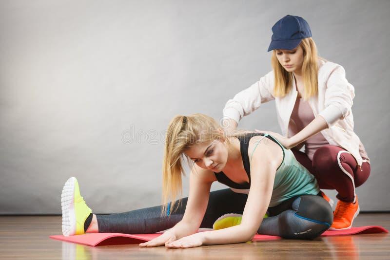 Γυναίκα sportswear στα πόδια τεντώματος με τον εκπαιδευτή στοκ φωτογραφίες