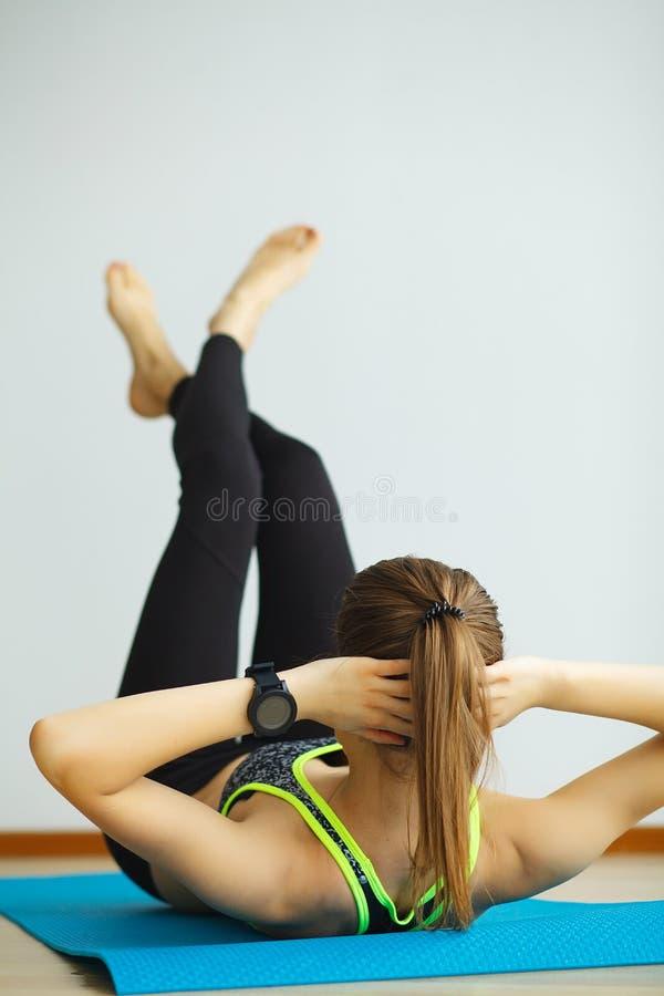 Γυναίκα sportswear στη συνεδρίαση στο έδαφος στοκ φωτογραφίες