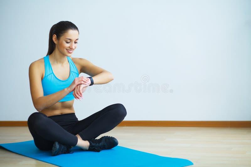 Γυναίκα sportswear στη συνεδρίαση στο έδαφος στοκ εικόνες με δικαίωμα ελεύθερης χρήσης