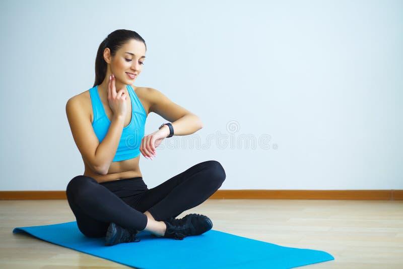 Γυναίκα sportswear στη συνεδρίαση στο έδαφος στοκ εικόνα με δικαίωμα ελεύθερης χρήσης