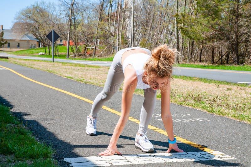 Γυναίκα Sprinter που παίρνει έτοιμη να αρχίσει στην τρέχοντας διαδρομή στοκ φωτογραφίες