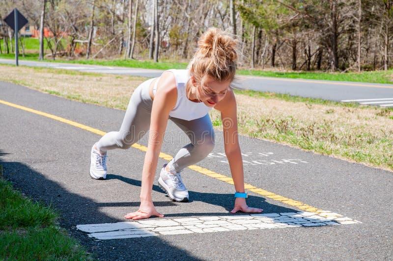 Γυναίκα Sprinter που παίρνει έτοιμη να αρχίσει στην τρέχοντας διαδρομή στοκ εικόνα