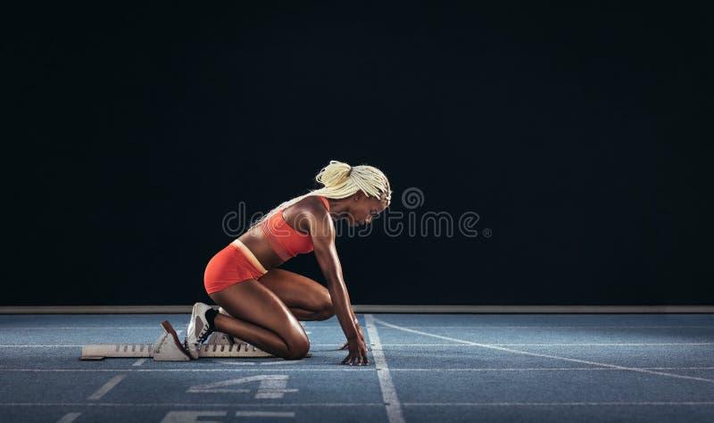 Γυναίκα sprinter που χρησιμοποιεί έναν αρχικό φραγμό για να αρχίσει την ορμή της σε ένα ρ στοκ φωτογραφία με δικαίωμα ελεύθερης χρήσης