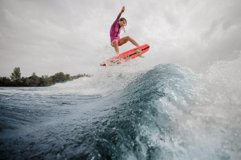 Γυναίκα wakesurfer που πηδά επάνω στο μπλε καταβρέχοντας κύμα ενάντια στον ουρανό στοκ εικόνες με δικαίωμα ελεύθερης χρήσης