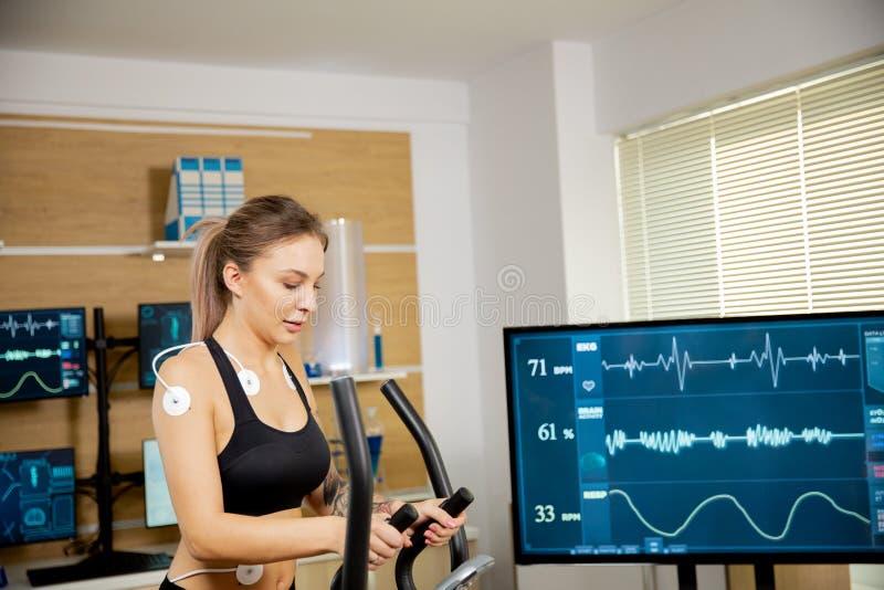 Γυναίκες αθλήτριες που κάνουν σωματική προσπάθεια στο στέρνο και έχουν ηλεκτρόδια προσδεδεμένα σε αυτό και τα αποτελέσματα φαίνον στοκ φωτογραφία