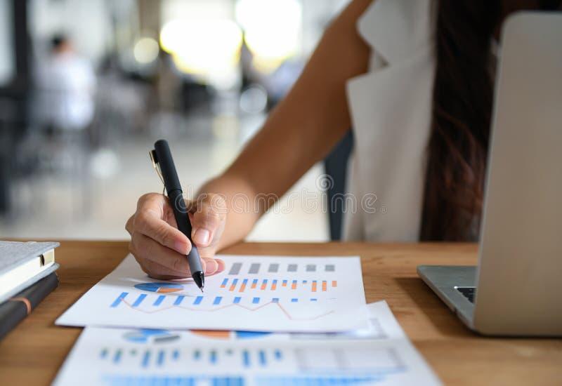 Γυναίκες επιχειρηματίες κατέδειξαν το στυλό στο διάγραμμα δεδομένων για ανάλυση Graph, φορητός υπολογιστής στο γραφείο στοκ φωτογραφία με δικαίωμα ελεύθερης χρήσης