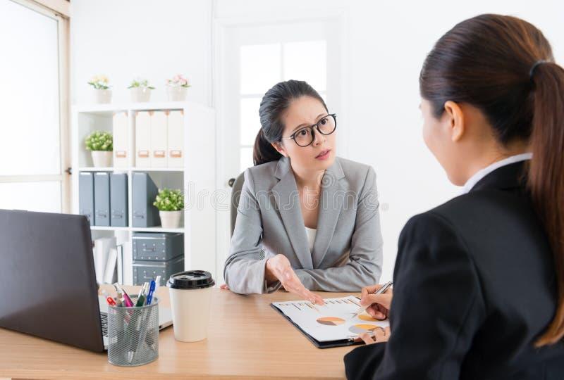 Γυναίκες επιχειρηματιών που διοργανώνουν τη συνεδρίαση στην αρχή στοκ φωτογραφία