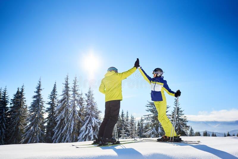 Γυναίκες και άνδρες σκιέρ υψώνουν πέντε ο ένας στον άλλο κάτω από τον ηλιόλουστο γαλάζιο ουρανό Επιτυχημένο σκι στην κορυφή του β στοκ εικόνα