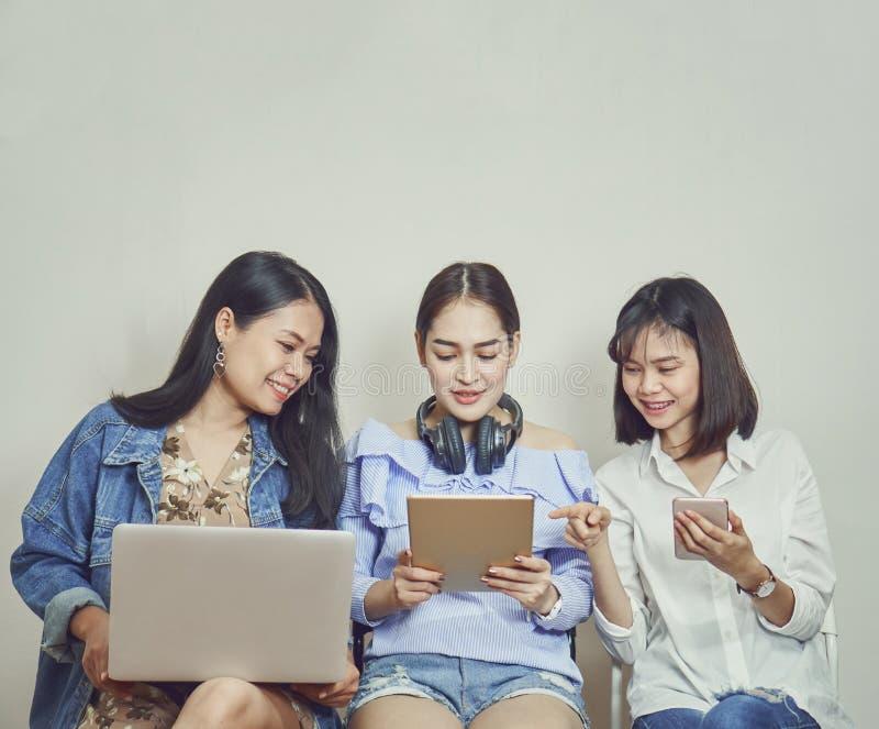 Γυναίκες και φίλοι χρησιμοποίηση του τηλεφώνου και του υπολογιστή στοκ εικόνες