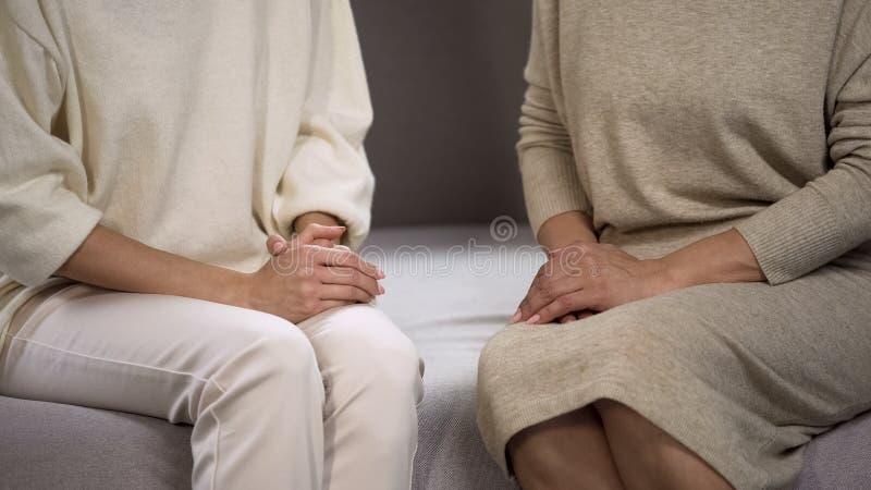 Γυναίκες κινηματογραφήσεων σε πρώτο πλάνο που κάθονται στον καναπέ που έχει τη σημαντική συνομιλία, οικογενειακές σχέσεις στοκ φωτογραφίες