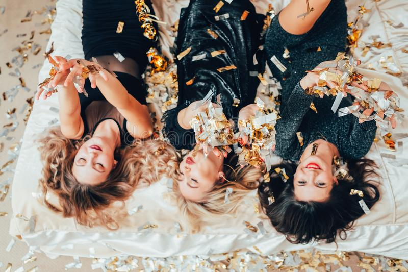 Γυναίκες κομμάτων θέματος που χαλαρώνουν τον ενθουσιασμό κομφετί κρεβατιών στοκ εικόνες με δικαίωμα ελεύθερης χρήσης