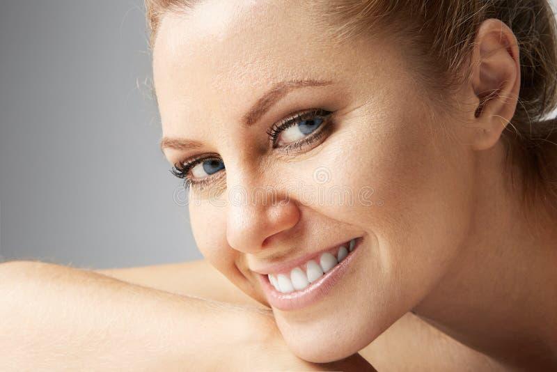 Γυναίκες ομορφιάς με τα μεγάλα μπλε μάτια και τα σκοτεινά φρύδια που εξετάζουν τη κάμερα και το χαμόγελο Πρότυπο με την ελαφριά n στοκ φωτογραφίες
