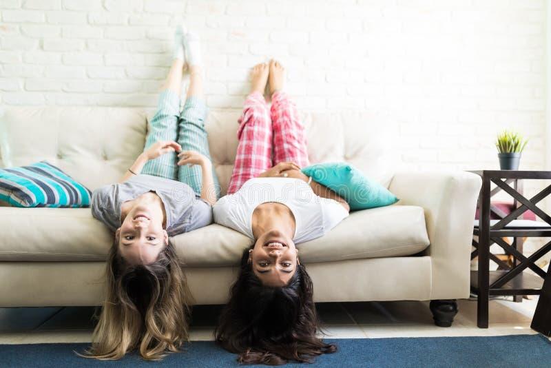 Γυναίκες που έχουν τη διασκέδαση ανάποδα στον καναπέ στοκ φωτογραφίες με δικαίωμα ελεύθερης χρήσης