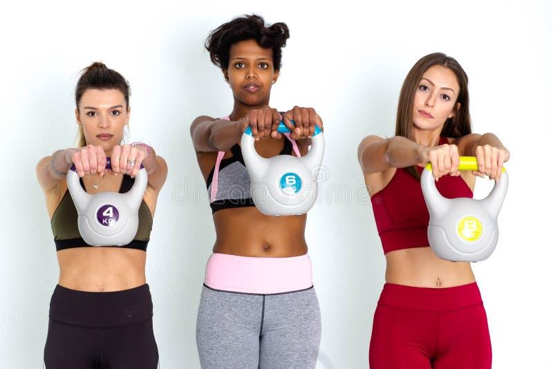 Γυναίκες που ανυψώνουν kettlebells Ομάδα θηλυκών αθλητών που ανυψώνουν kettlebells - εικόνα στοκ εικόνες